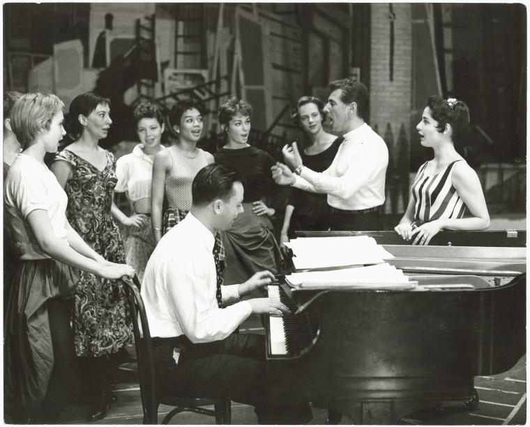 Stephen Sondheim on piano with Leonard Bernstein and Carol Lawrence (on far right) standing amongst female singers rehearsing for the stage production West Side Story (The New York Public Library Digital Collections. 1957).